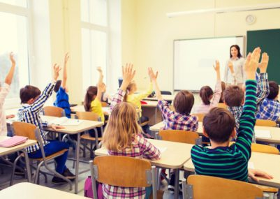 group-of-school-kids-with-teacher-sitting-in-classroom-and-raising-hands-1
